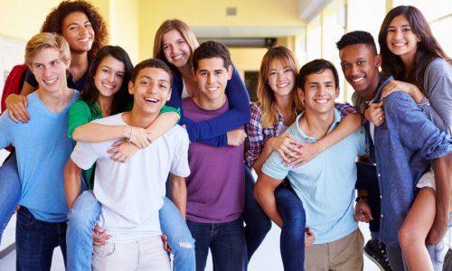 Group Of High School Students Giving Piggybacks In Corridor